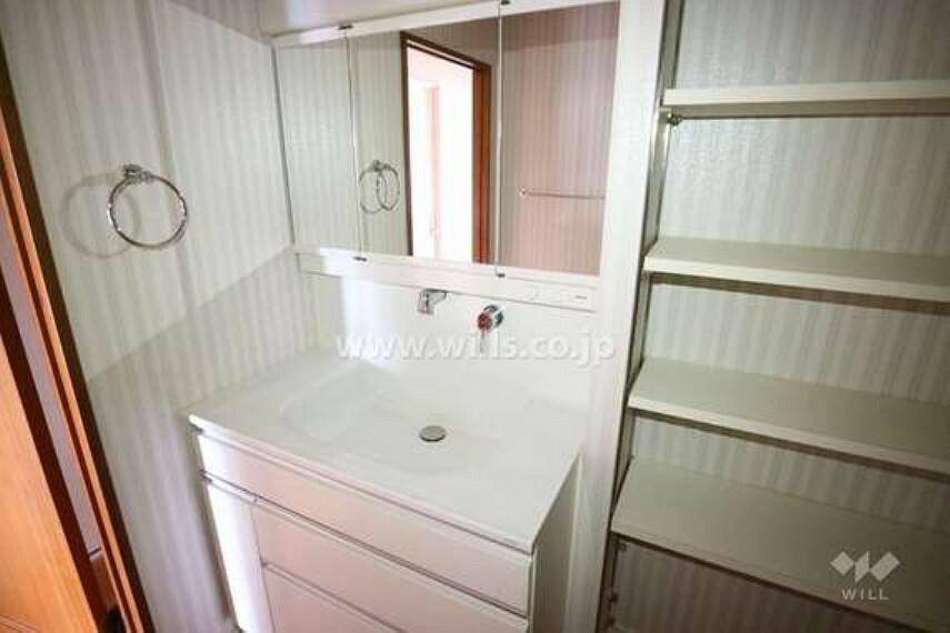 洗面化粧台 収納スペースがたっぷりな洗面室です。三面鏡付きの洗面台で、鏡の裏、ボウルの下に加え、洗面台横に棚が設けられており、細々した物から大きな物までたくさん収納できます。