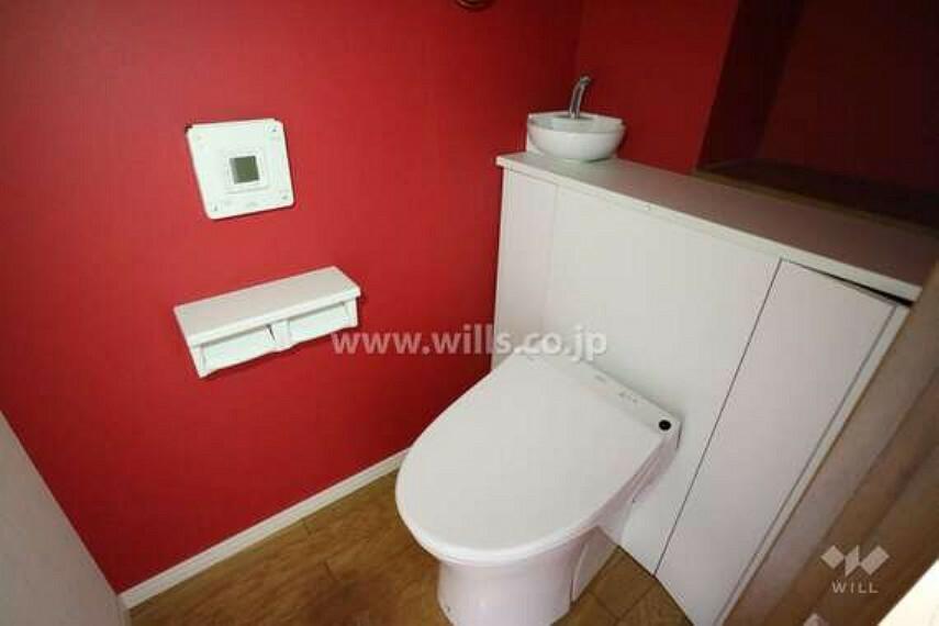 トイレ お手洗いの様子。鮮やかなカラーのクロスにより、明るい雰囲気があります。収納付きなので何かと小物を隠して収納しておくことができて便利です。