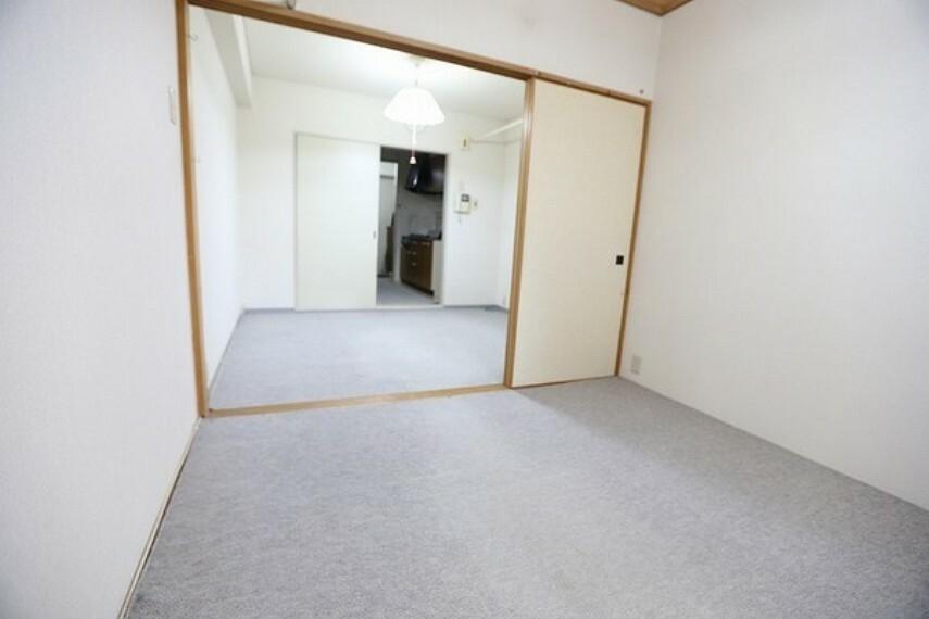 洋室 和室(カーペット敷き)のお部屋から洋室、キッチン、玄関部分を見た画像になります。 扉を開ければ1つの部屋として広々と利用することの出来る間取りです。