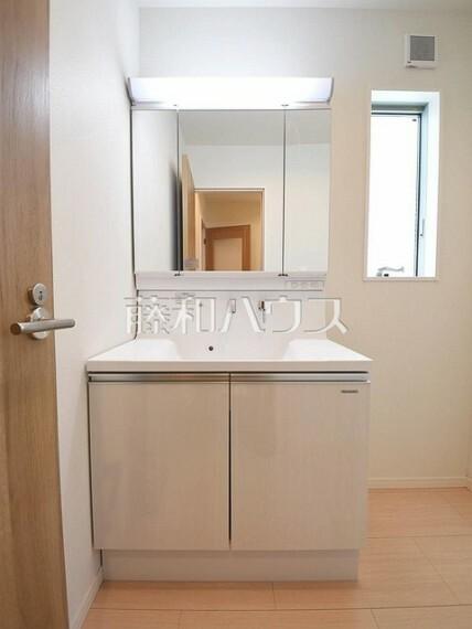 洗面化粧台 1号棟 三面鏡付きの洗面台。鏡の裏にも収納があり、歯ブラシや化粧品等もすっきり収納できます。 【府中市小柳町5丁目】