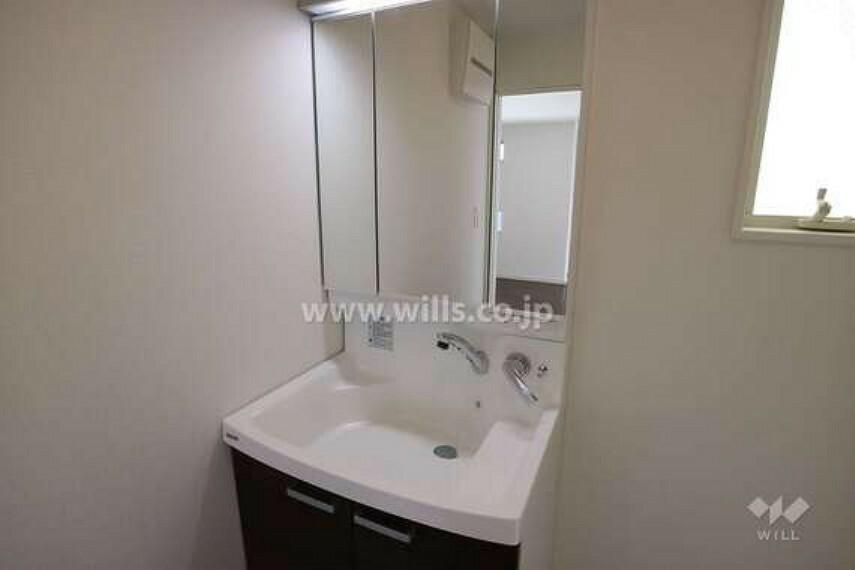 洗面化粧台 洗面室の様子。三面鏡付きの洗面台です。鏡の裏、ボウルの下、双方に収納スペースがあるため、いろんな小物を隠して収納できます。