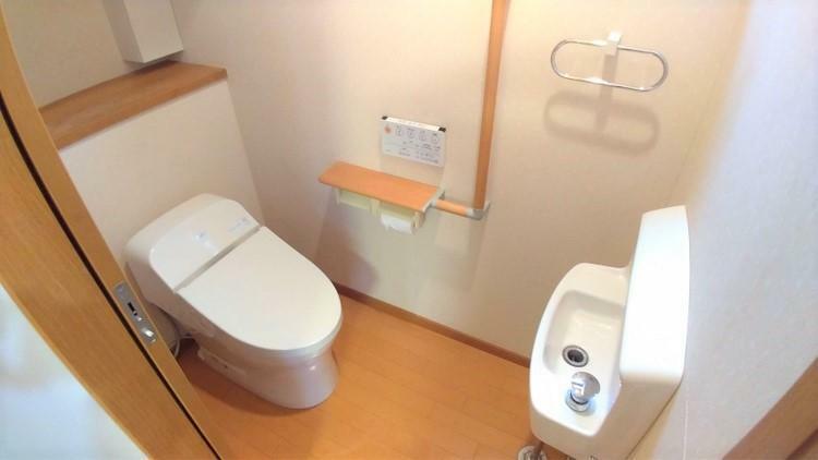 トイレ タンクレスでスッキリとしたトイレスペース。小型の手洗い器が正面にあり使いやすいレイアウト。