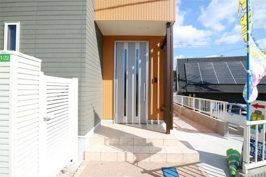 玄関 ポップなオレンジのと引き立つシャープな印象のシルバーの玄関ドア。