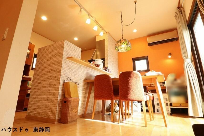 居間・リビング 可愛らしいタイルを施したキッチンカウンター オレンジ色のアクセントクロスと合わせてほんわか柔らかい印象のダイニングです