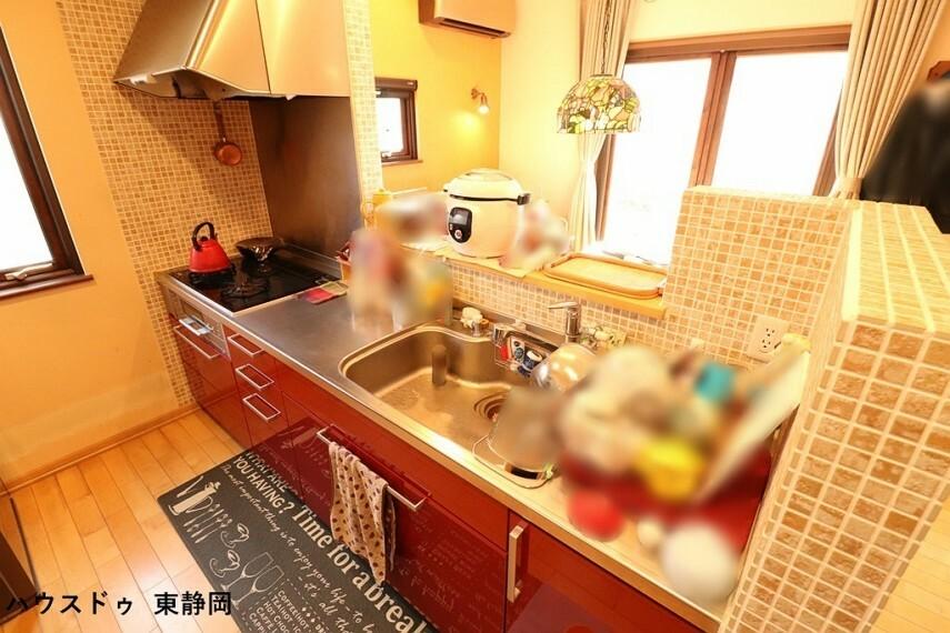 キッチン 赤色が華やかな印象のシステムキッチン カウンターの開口部が広く、開放的なキッチンです。