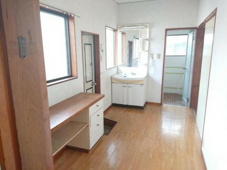 洗面化粧台 【リフォーム前写真】洗面脱衣室も他の居室同様にフロアの重ね張りやクロスの張替え工事を行います。広々とした空間で、扉を2か所設けているため動線が良いです。