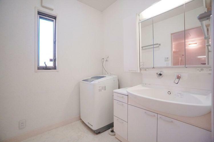 洗面化粧台 こちらは2階の洗面室&洗濯機置き場です。スペースにゆとりがあり、洗面台も大きく収納も豊富。窓から入る自然の光で室内も明るく使いやすいですね。