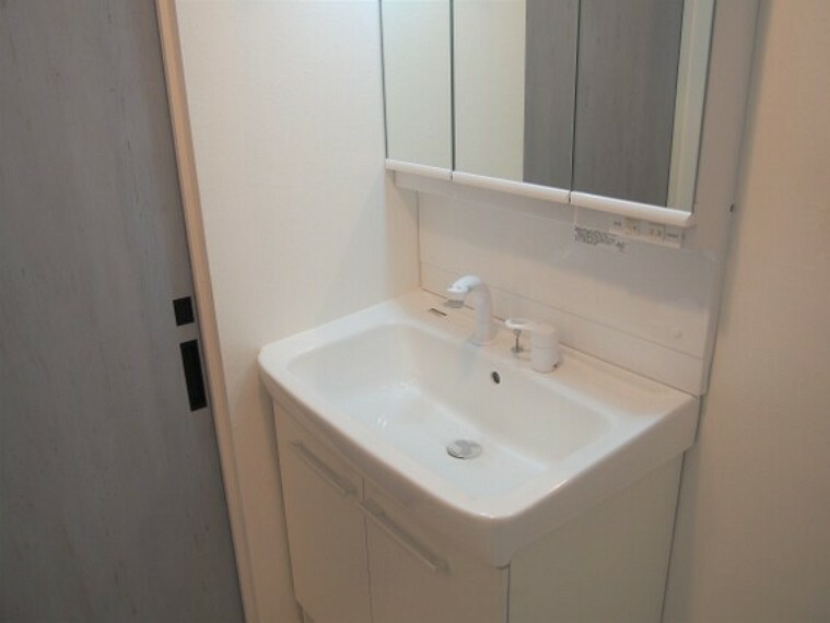 洗面化粧台 三面鏡を備えた洗面台。