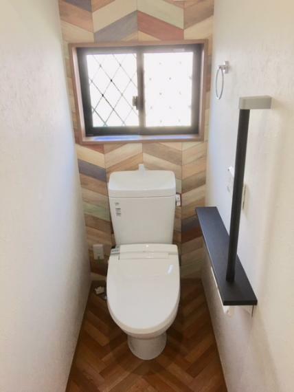 同仕様写真(内観) アクセントクロスを用いてオシャレな空間に仕上げました。手すりや飾り棚も設けた使い勝手のよいトイレです。