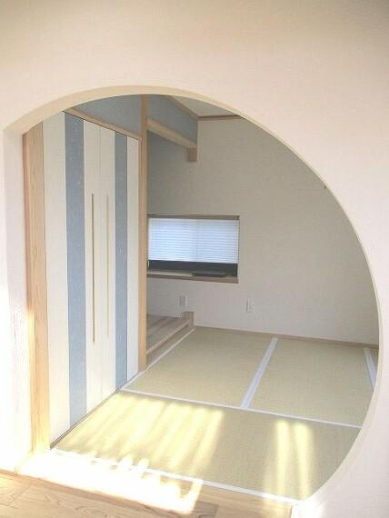 和室 丸い出入口とポップな色使いの温かみのある和室