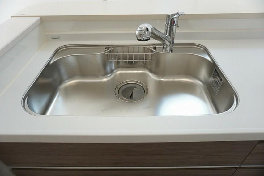キッチン 同仕様写真。大きな鍋などもラクラク洗えるワイドサイズを採用。排水口が奥なので水の流れもスムーズです。浄水器内蔵型シャワー水栓つき。
