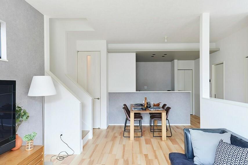 居間・リビング モデルハウス1号棟/ダイニング  キッチンやリビングのアクセントクロスが落ち着いた空間を演出します。中央に明かりとりの小窓がある、すっきりとしたデザインのリビングドアを採用しました。(※2021年7月撮影)