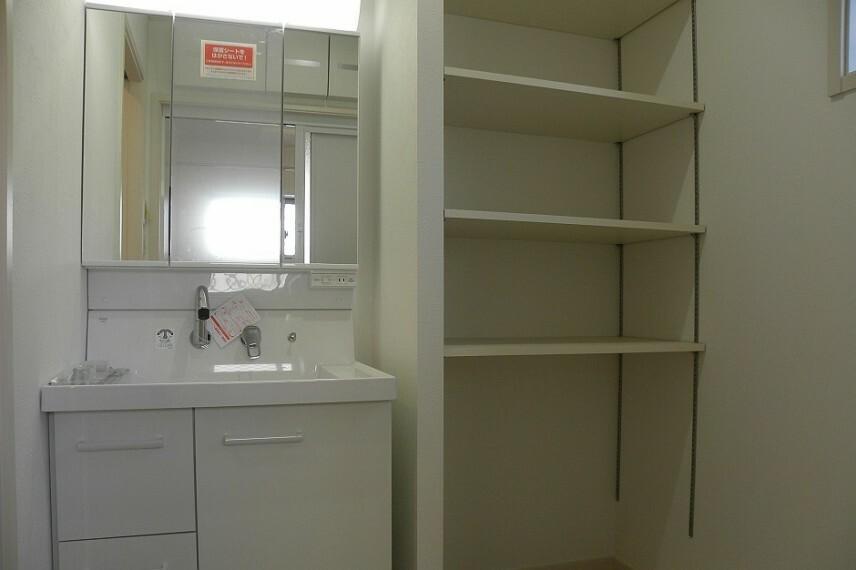洗面化粧台 三面鏡の鏡もあり、隣には備え付けの収納が付いてます。高さのあるものから小物まで幅広く収納することができます。