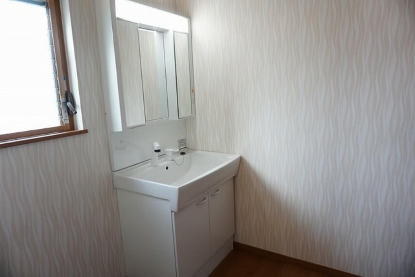 洗面化粧台 「同仕様写真」シャワーホース付のシャンプードレッサー。鏡付きで毎朝の支度もはかどります。歯みがきセットや化粧品もきれいに整頓できますよ。