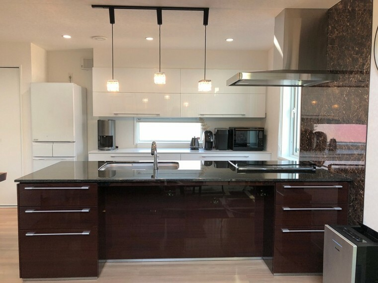 キッチン ピアノ鏡面塗装の扉・天然御影石カウンターのオープンキッチンが、高級感がありシンプルな演出をしております。