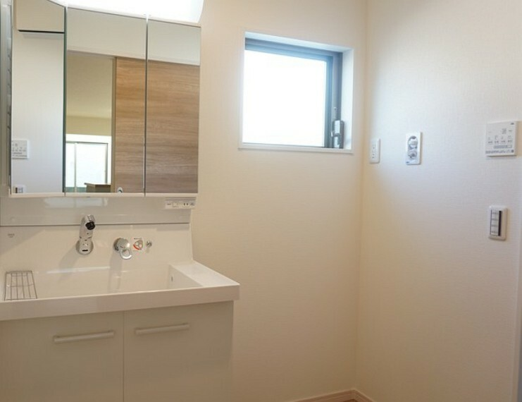 洗面化粧台 同仕様写真。ミラー扉の内側が収納スペースになっていて歯みがきセットや化粧品もきれいに整頓できますよ。シャワーホース付のシャンプードレッサーで毎朝の支度もはかどります。