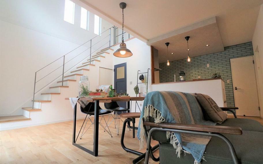 居間・リビング 施工例■リビングダイニングからは吹抜階段がたくさんの光を取り込み開放的な空間を演出します。一方、キッチン上はあえて天井を下げてグレーのクロスを使うことで空間のアクセントに。