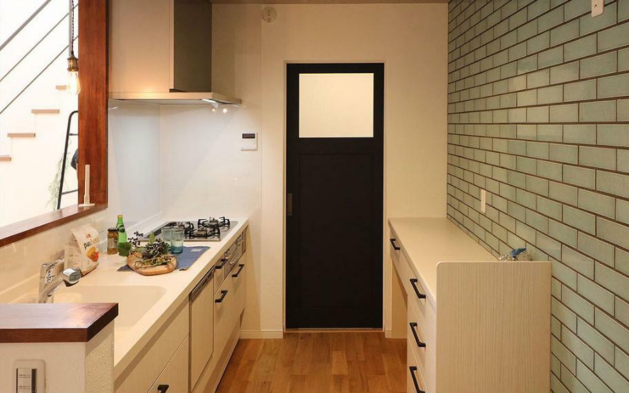 キッチン 施工例■背面壁に凹凸感のあるタイルはったキッチンは、あたたかみのあるカウンター部分の木や、ドアの質感がおしゃれな空間に。