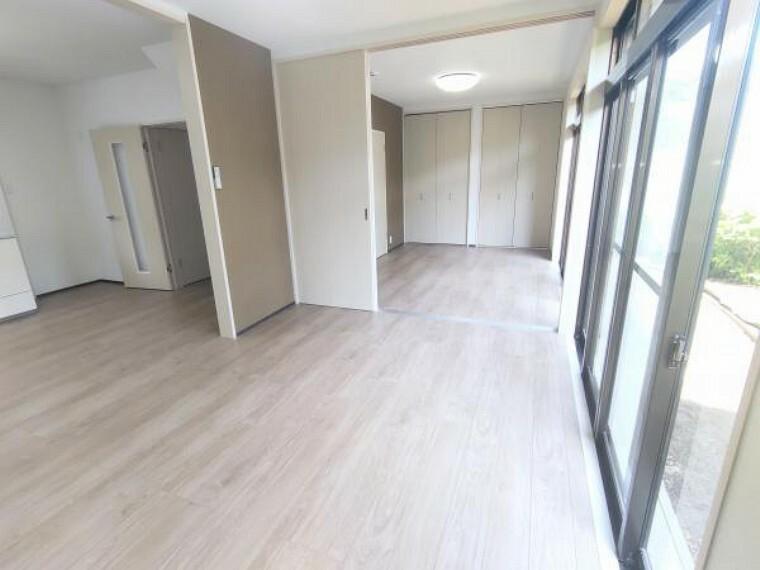 【リビング:リフォーム済写真】リビングから洋室を見た画角です。仕切りのドアの背が高く、部屋が広く見えますね。このドアは外して洋室のクローゼットにしまえる設計になっているので、さらに広く見せたいときにおススメです。