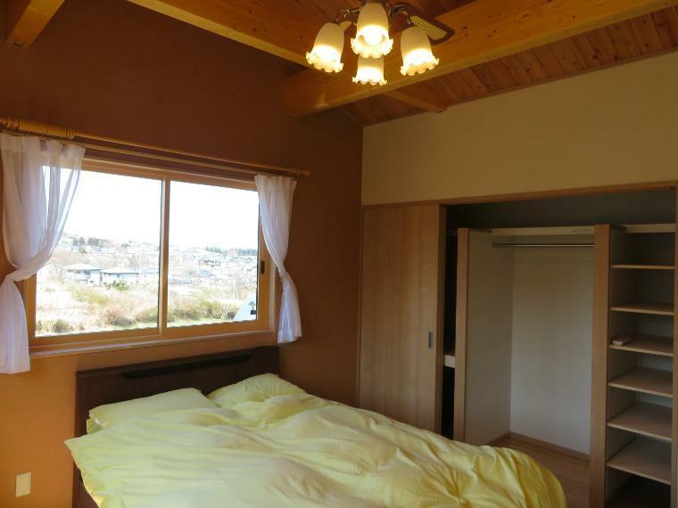 寝室 勾配天井の主寝室。収納の中にも細かく収納できる棚がついていて、とても便利です。