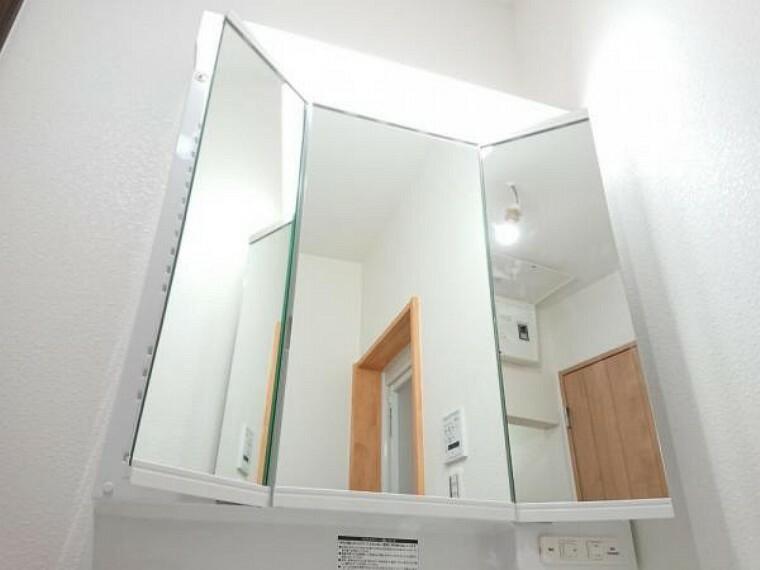 洗面化粧台 【三面鏡】新品の洗面台は三面鏡になっています。鏡の裏に化粧品を収納できるだけでなく、毎朝の身だしなみチェックも後ろまで見ることができるので便利です。照明も左右に付いているのでとても明るいです。