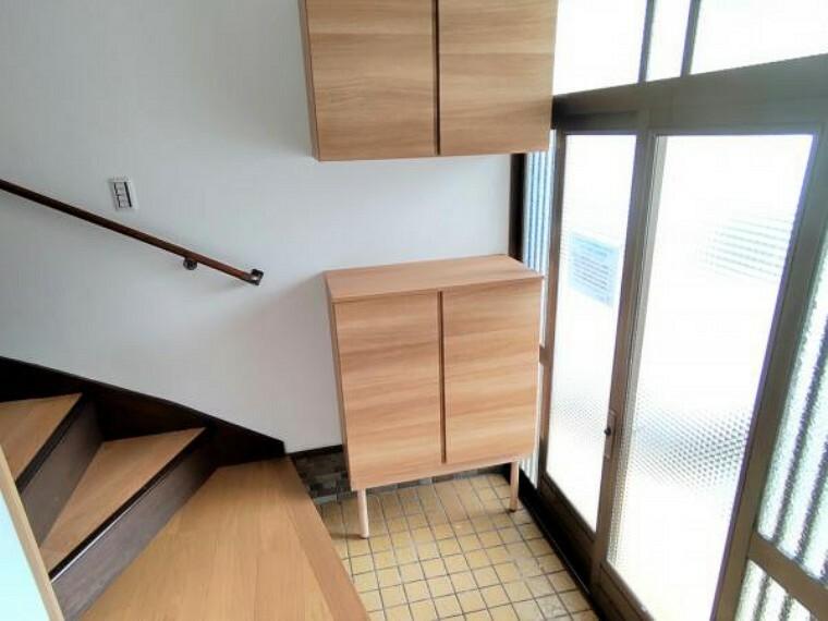 【玄関:リフォーム済写真】床はフローリングを上張りし、壁と天井はクロスの張り替えを行いました。シューズボックスは永大産業製の新品に交換しました。