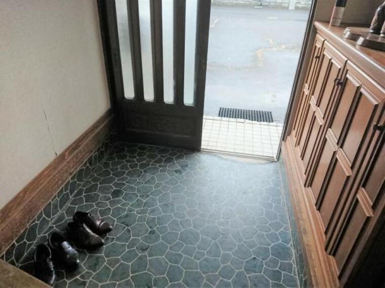 現況写真 【リフォーム前】玄関ドアに交換し、玄関内のポーチタイルを張替えます。既存の下駄箱を撤去しシューズボックスを新設する計画です。