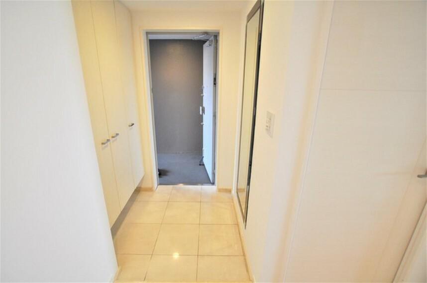 玄関 タイル張りで大型の収納と鏡がある広い玄関です。