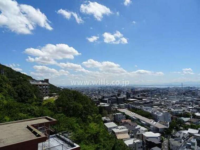 外観写真 ザ・岡本プレミアムの遠景。南斜面の高台にあり、周囲は緑に囲まれています。