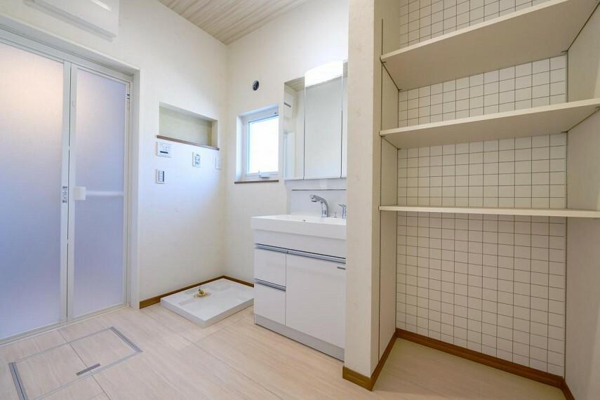 洗面化粧台 【C号地 洗面室】洗面室に設けた可動棚は、洗剤のストックやタオルを収納しておくのに重宝します。家族みんなの下着やパジャマを収納しておくと入浴の時に便利です。