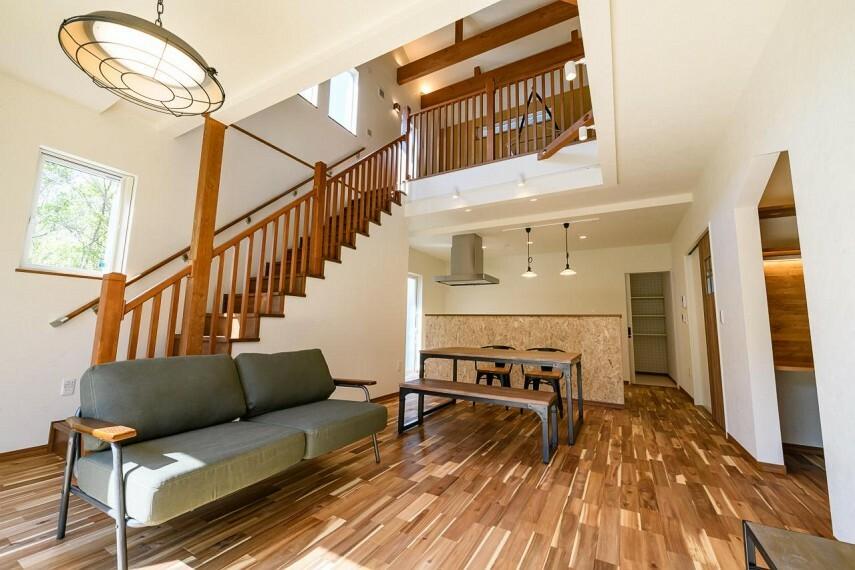 現況外観写真 【C号地 LDK】ログハウス風の吹き抜けLDK 梁と階段の手すり、吹き抜けの壁を木の味わいを活かした作りに。まさにアウトドアライクな生活を楽しめそうな明るく居心地の良いLDKです。