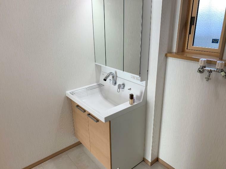 脱衣場 三面鏡の洗面化粧台。鏡の裏は小物を収納できるようになっています。