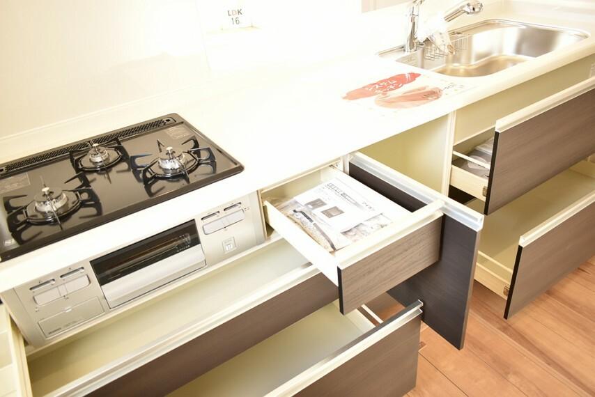 キッチン 施工例 3口コンロ、魚焼きグリル付きのシステムキッチンです フライパンや鍋の収納にも便利なキッチン収納付きです