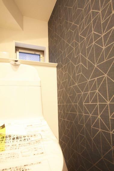 トイレ 【トイレ-アクセント】 ホワイトのシンプルな空間に、ダークグレーのアクセントクロスがあるだけで、ホテルのような品のある空間に!ぜひご見学の際に、ご覧ください!
