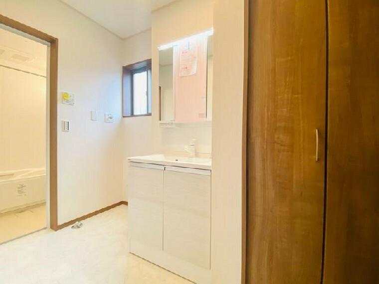 B号棟 洗面室~内覧いただけます~・・・収納も兼ねた三面鏡で、散らかりがちな水廻りもすっきりお片づけ出来ます。さらに、タオルや衣類等が置いておける収納を設置しましたので室内を広く使えますね。