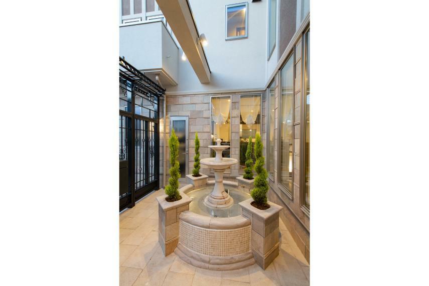 現況外観写真 家の中心に位置する中庭には、ホテルのエントランスを彷彿とさせる豪華な水のモニュメントとなる噴水を採用。 (A号棟)