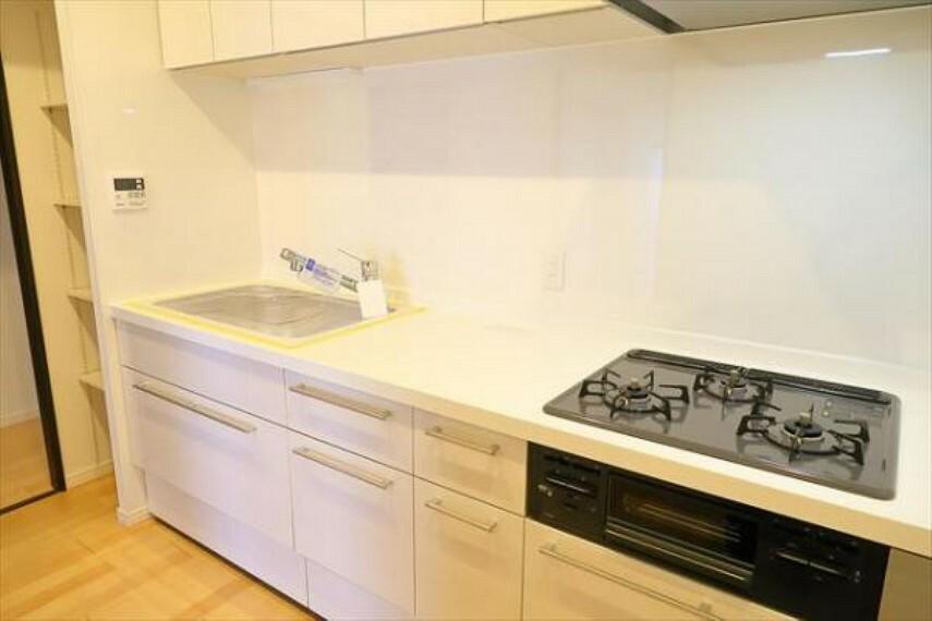 キッチン 3つのコンロで同時に調理ができるので、三ツ口コンロの使いやすいシステムキッチンを採用。
