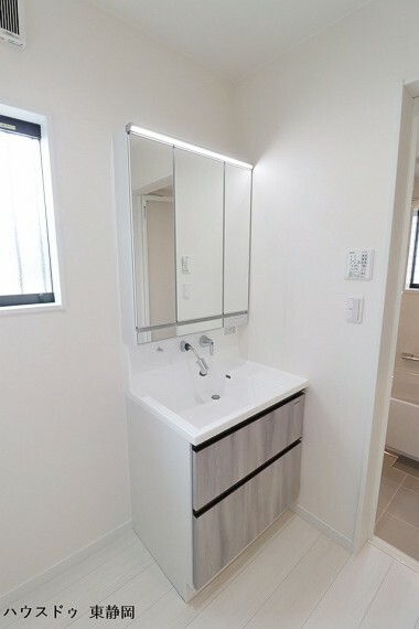 洗面化粧台 鏡の中の収納で、家族の小物の集まる洗面所もスッキリ。壁面取り付けの蛇口は、伸縮自在なシャワーヘッドタイプを採用。