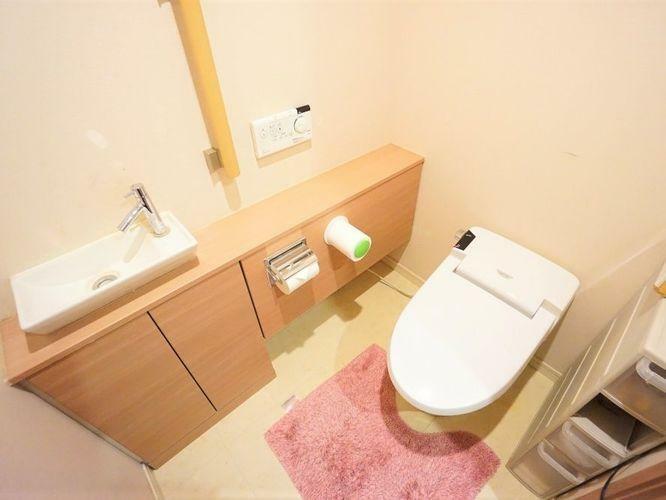 トイレ タンクレスのトイレでゆったりとした空間になっています。別途で手洗いがあり、収納スペースも沢山あります。手摺も付いているので足腰が弱っているときでも安心ですね。