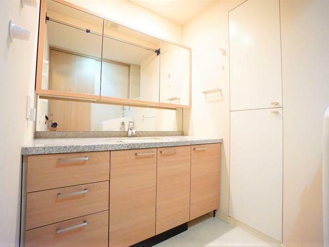 洗面化粧台 ワイドな洗面台で、二人並んでもゆとりがあります。大きな三面鏡も収納がたっぷりあり、家族全員のスキンケア用品を置いても余裕です。リネン庫がありタオルや消耗品の置き場に困ることはありません。