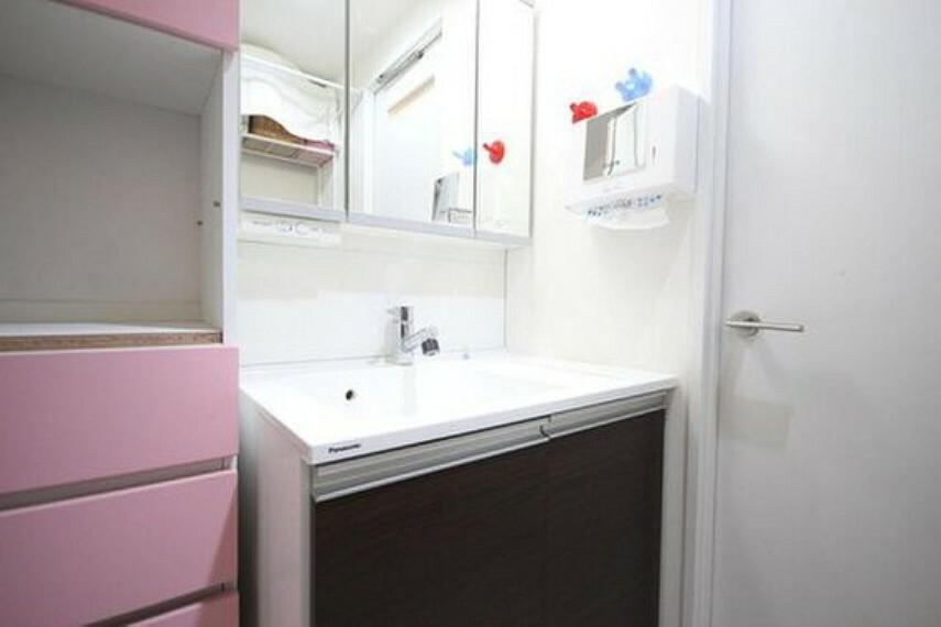 洗面化粧台 大きく見やすい三面鏡で清潔感ある洗面台は、身だしなみチェックや肌のお手入れに最適です。何かとに物が増える場所だからこそ、スッキリと見映えの良い空間に拵えました。