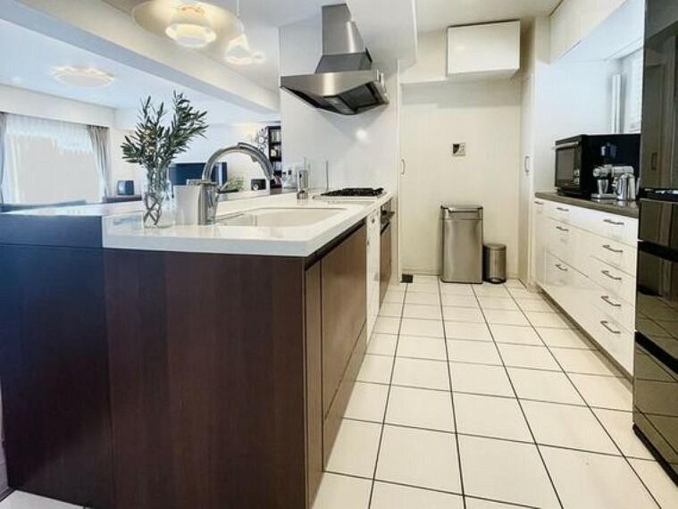 キッチン 白いタイル張りの清潔感のあるキッチン。背面キャビネットとの間は1.25mを確保。2名以上での調理にもゆとりがあります。