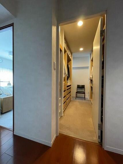 ウォークインクローゼット ワードローブ家具が備え付けられた機能的なクローゼットは、奥で寝室につながっています。