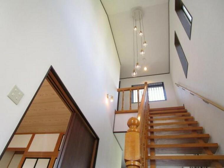 【リフォーム済】玄関入ってすぐにある階段と吹き抜けです。東側に明かり窓がついており、明るい空間となっています。天井と壁のクロスを張り替え、手すりを新設しました。大光電機製のペンダントライトを新設しました。