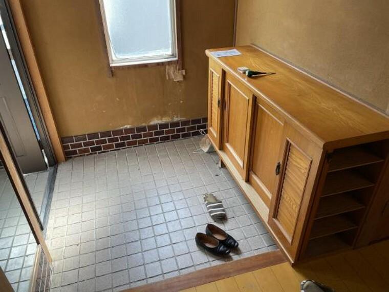 【リフォーム中】玄関ホールの写真です。壁天井はホワイト系クロスに張り替え、床も一面フローリングを張り替えます。また、照明や大型のシューズボックスも新設してお客様を気持ちよく迎えられる玄関に仕上げます。