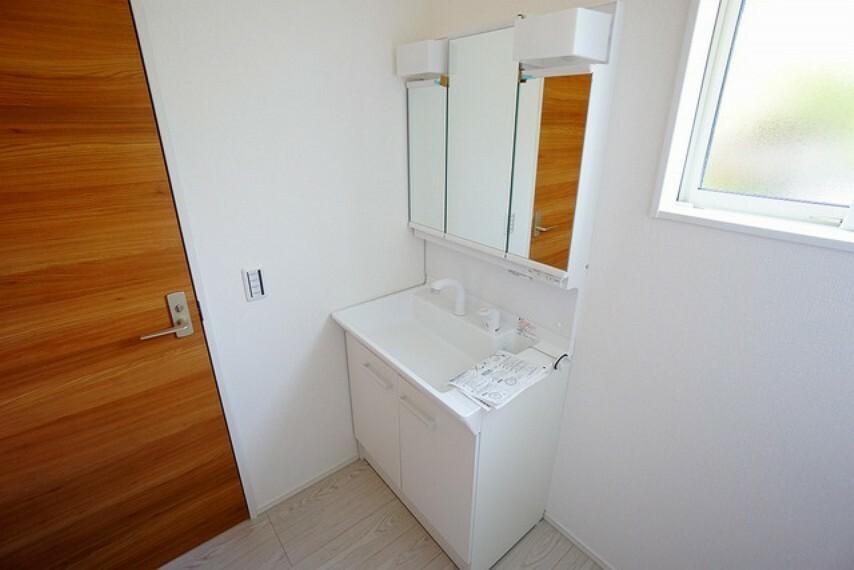 洗面化粧台 三面鏡付きの洗面台。白くて清潔感がありますね。コンパクトですがたくさん収納できますよ。