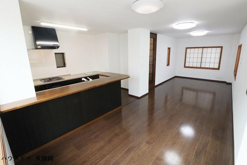 居間・リビング 2021年5月リフォーム完了!白のクロスにダークトーンのキッチンとフローリングの映えるリビングです。