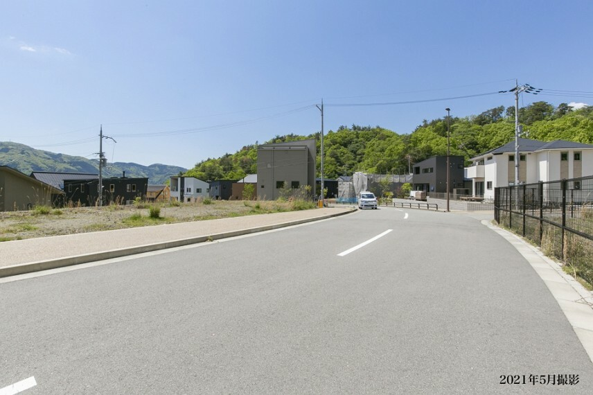 現況写真 北西側前面道路の幅員は約10.5m(歩道を含む)。緩いカーブになっており、車のスピードも自然と抑えられるので安心です。道なりにゆったり下るとタウン内の中心部へ続きます。/2021年5月撮影