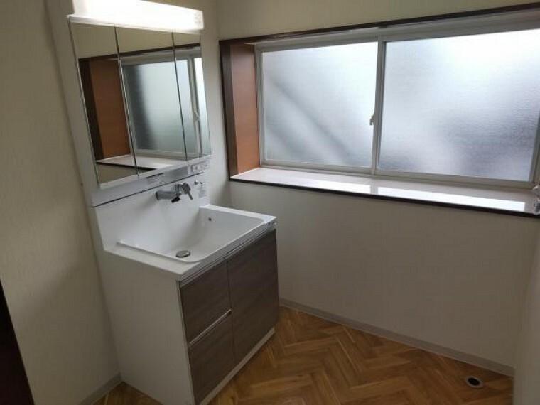 【リフォーム後写真】脱衣場になります。ハウステック製の三面鏡仕様洗面化粧台は収納も充実しています。床はクッションフロアー張替え、天井、壁はクロス張替えを行いました。
