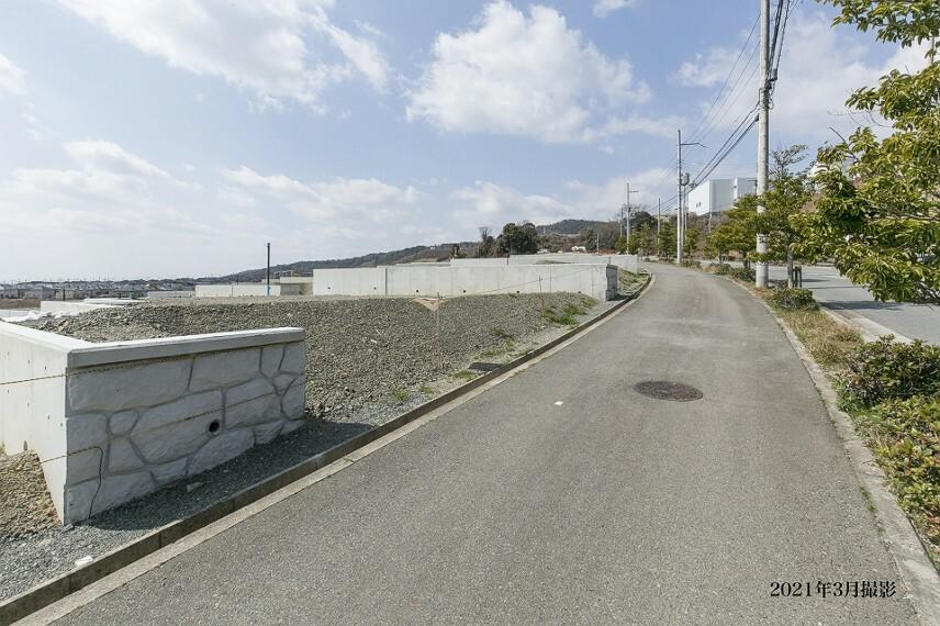 現況写真 【3-7、3-8号地 北側道路】 両サイドの歩道を含み、幅員約16.0mの広い道路です。道路沿いに「彩都やまぶき五丁目」バス停があり、「千里中央」駅へのアクセスに便利です。/2021年3月撮影